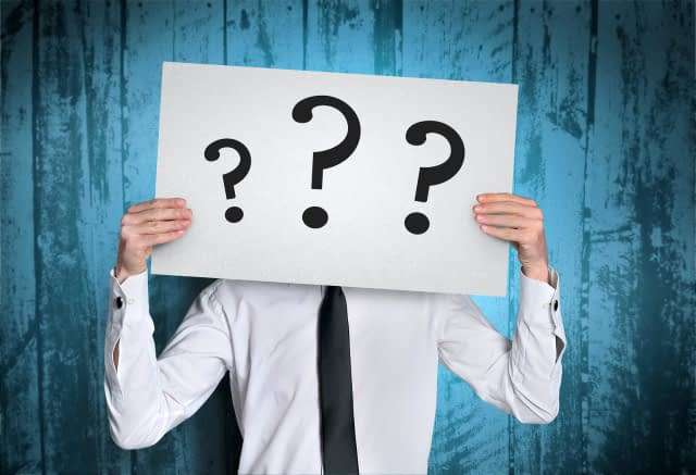 Business man cover face with question  board