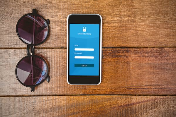 Online banking against view of glasses and a smartphone