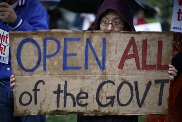 (Pictured) A protester holds up a sign calling for an end to the U.S. government shutdown on Capitol Hill in Washington, Oct. 10. Reuters